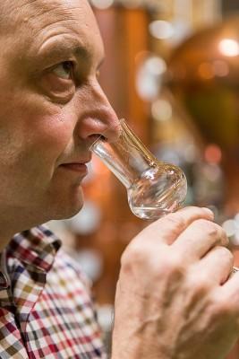 Abb. Karl Schroll, an einem Degustierglas in seiner Rechten riechend.